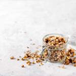 Raw honey nut granola in bale jar, lid open on grey fabric