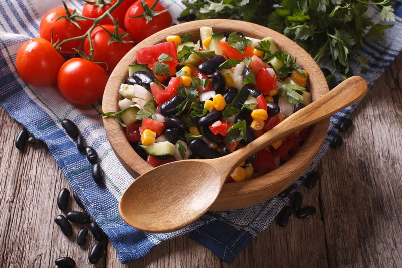 Summer Salsa in wooden bowl with spoon with fresh tomotoes and a kitchen towel on wooden table