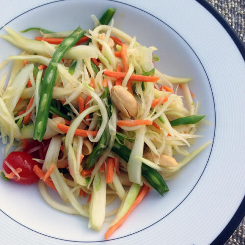 thai green papaya salad with green beans, tomatoes, peanuts, with a tangy pungent chili lime dressing in white bowl on placemat