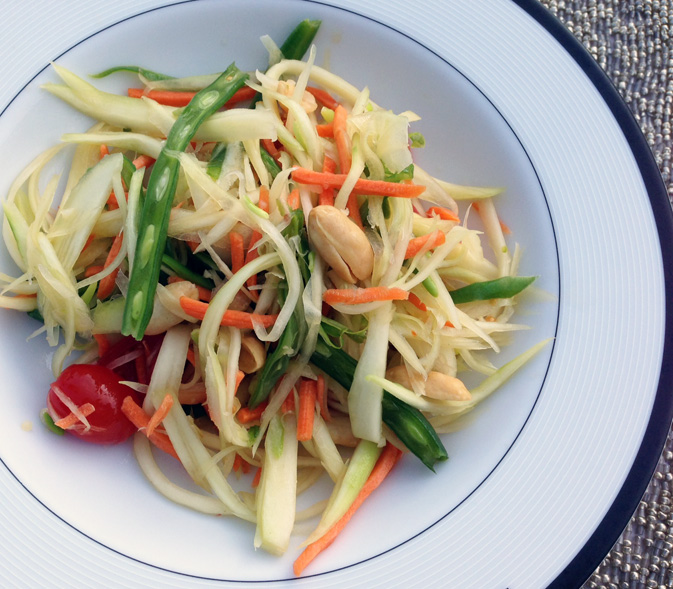 Learn how to make this easy and delicious papaya salad with green beans, tomatoes, peanuts, and dried shrimp with a tangy pungent chili lime dressing.
