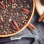 This honey pecan piePecan pie, nut crusher on table from above