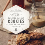 Oatmeal cookies on paper accompanied by raw ingredients on wood kitchen table