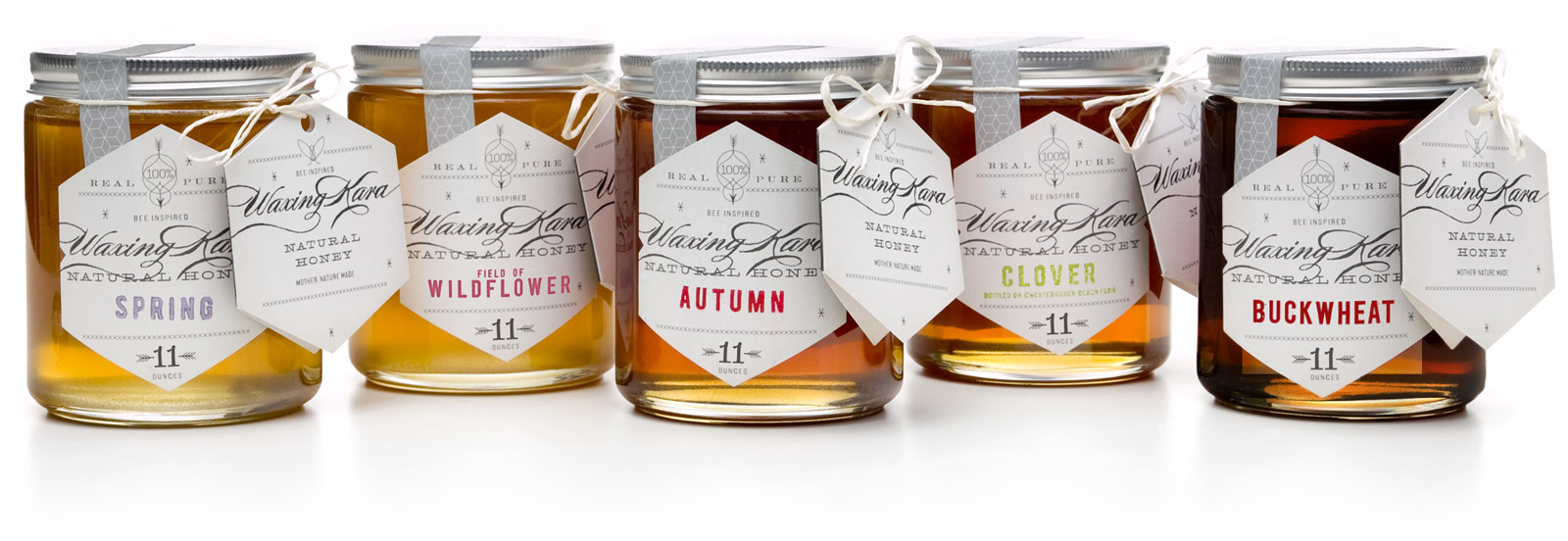 Jars of Spring, Wildflower, Autumn, Clover, and Buckwheat Waxing Kara Eastern Shore Kosher Honey lined up against a white editorial background