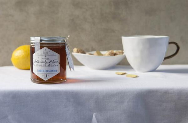 Honey, Lemon and Ginger Tea with tea cup, lemon and jar of honey on table