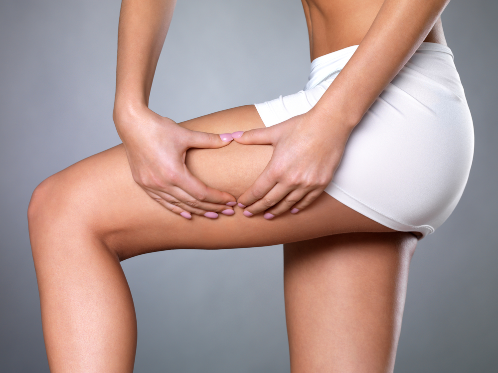 image of womans trunk, squeezing cellulite as she examines her skin prior to dry brushing skin
