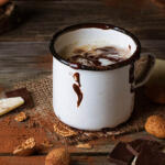 Dairy-Free Hot Cocoa on wood table surrounded by ingredients
