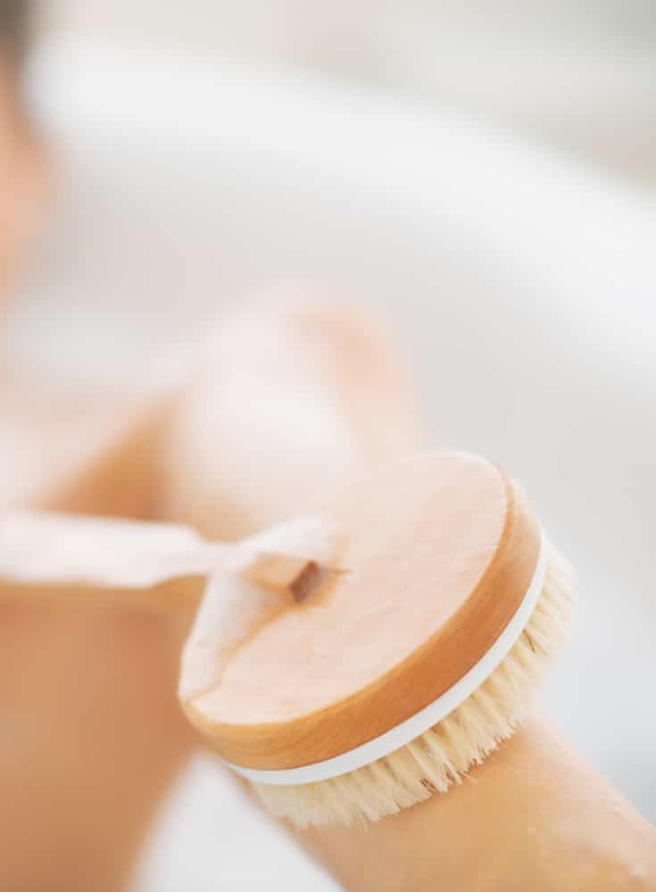 A dry brush being used on the legs in a bath tub