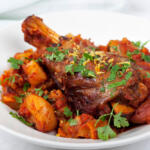 lamb shank on plate with carrots on a white plate