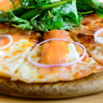 Smoked Salmon Pizza on serving board closeup topped with with raw onion rings and arugula salad