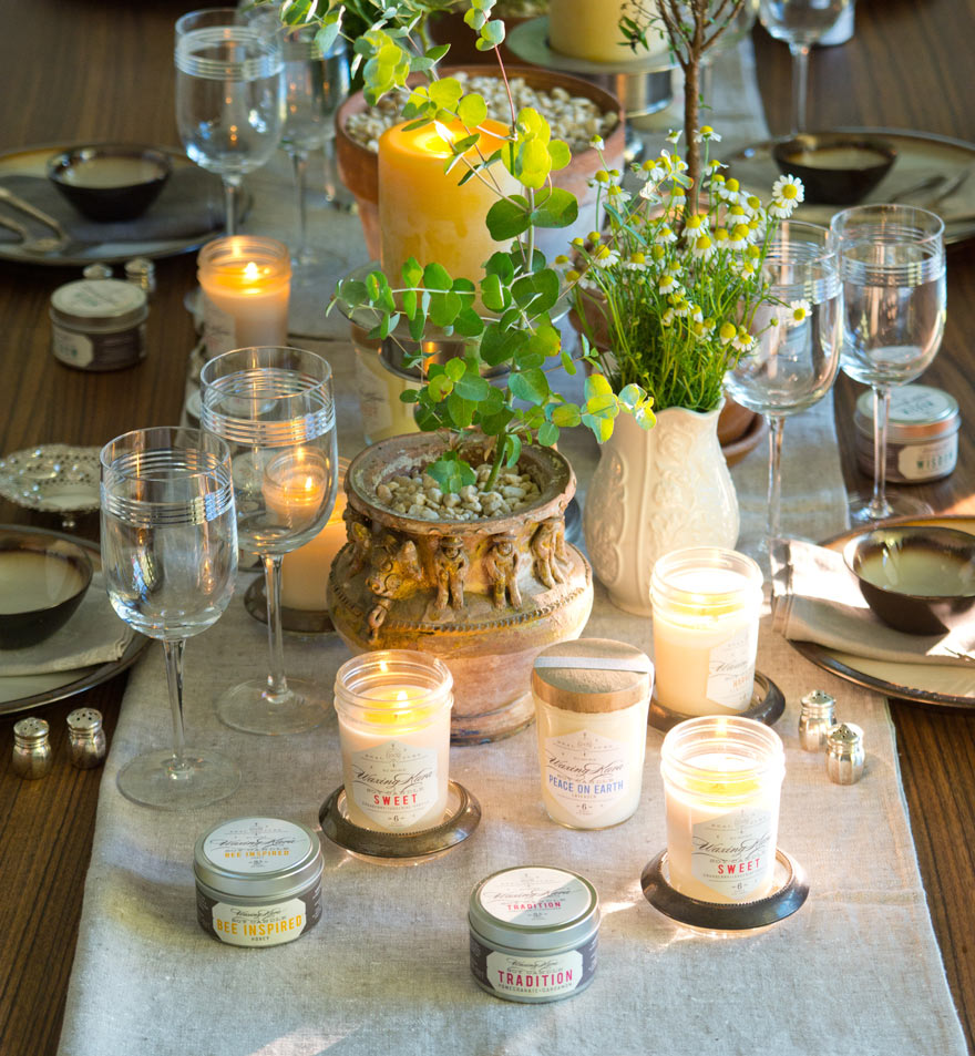 Candle setting with waxing kara candles on dining table. Linen runner on table.