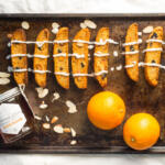 Cranberry Orange Biscotti on baking sheet with Waxing Kara Orange Blossom Honey and 2 oranges
