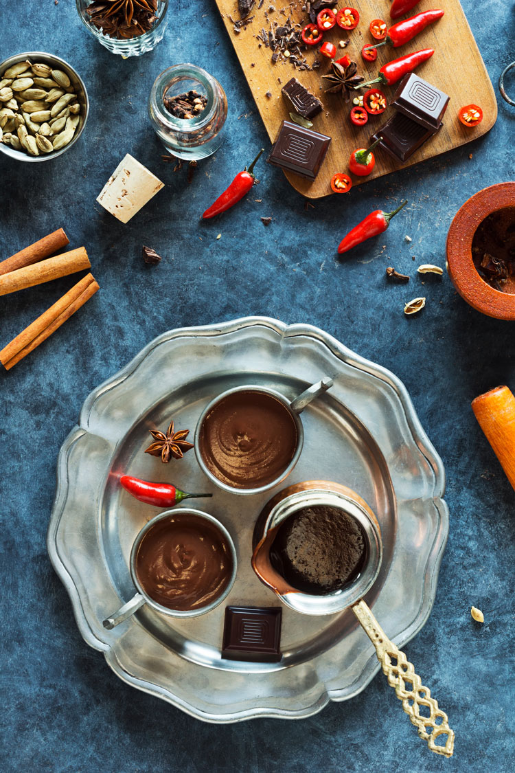 Overhead image of cinnamon, cocoa, hot peppers, cardamom, star anise and pewter tray with three cups of mexican hot cocoa on blue table learning how to make mexican hot cocoa