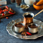 tray holding mexican hot cocoa and two tin cups surrounded by ingredients to learn how to make mexican hot cocoa on blue table