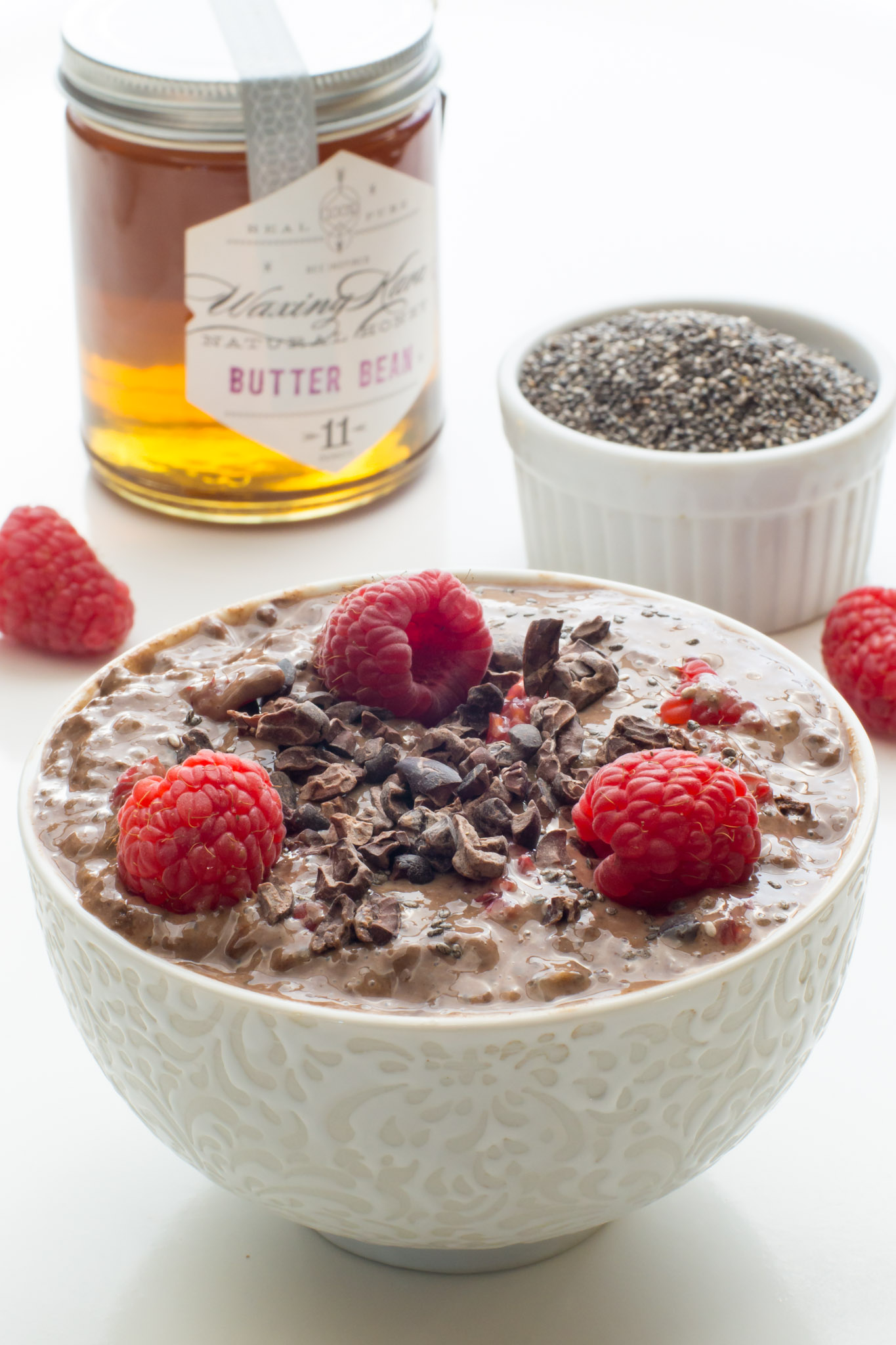 Chocolate Raspberry Chia Pudding in bowl with chia seeds and butter bean honey from waxing kara on the counter
