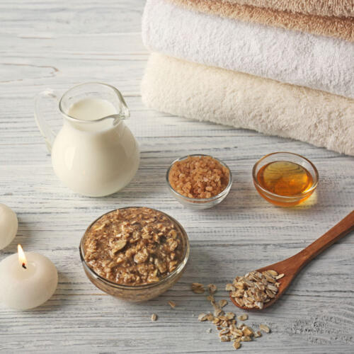ingredients for making an oat bath with milk and honey bath on table