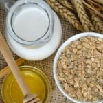 milk honey and oatmeal on a table with raw grain for oats recipes