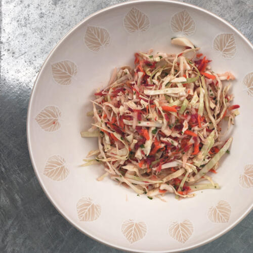 Healthy slaw in white bowl on metal table