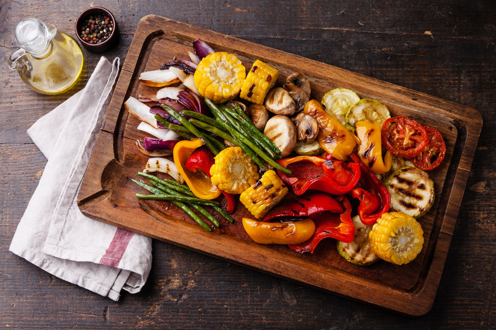 Summer Grilling Vegetables on a wood platter with a napkin and olive oil, in time for National Vegetarian Month