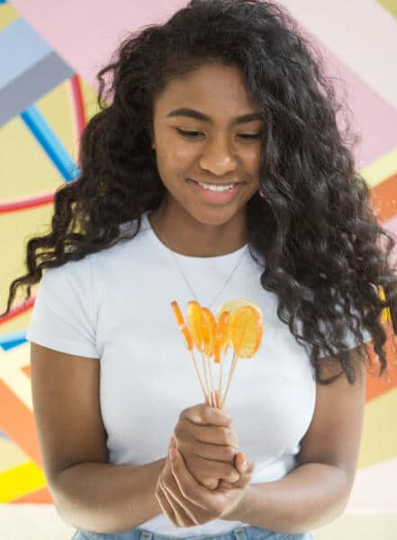 Picture of a beautiful young woman holding a bunch of honey lollipops in her hands