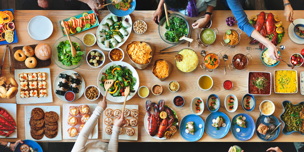 Ideas for Mother's Day Brunch overhead of large picnic table filled with food and friends reaching in to fill their plate