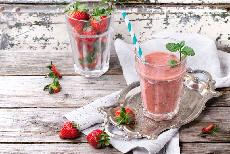 strawberry smoothie with mint garnish on weathered wood table