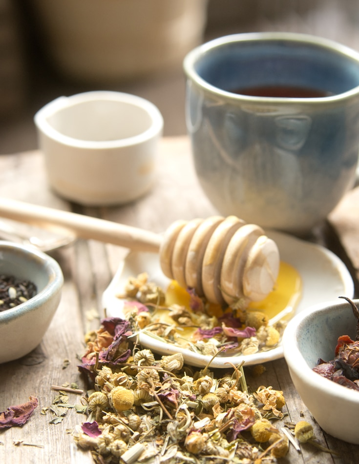 Assortment of teas and honey and tea cup on dining table