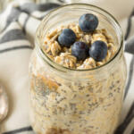 Berry Nutty Overnight Oats on striped towel with silver spoon