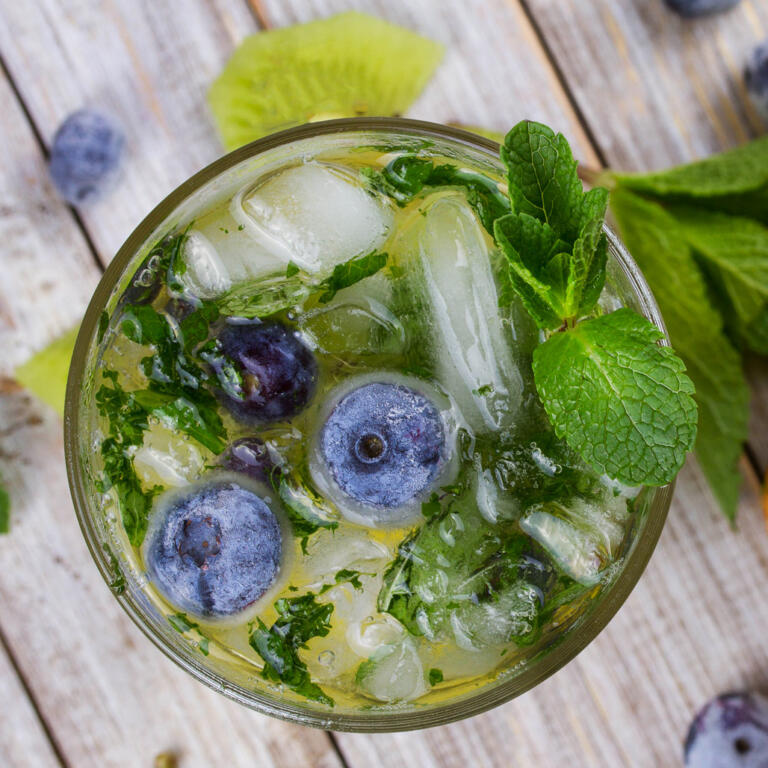 honey mojito with fresh blueberries in rocks glass on pier