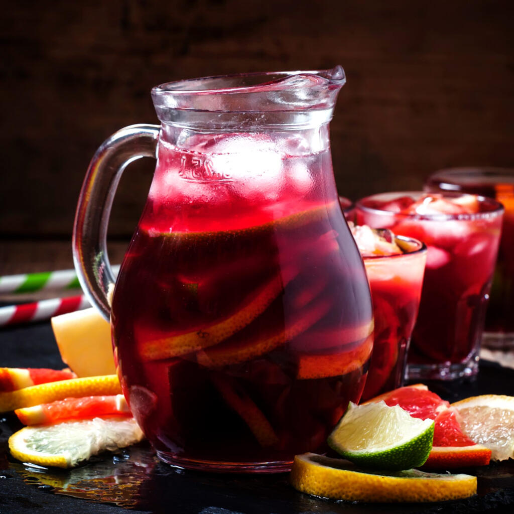 honey sangria in pitcher with fresh fruit and ice surrounded by fresh fruit