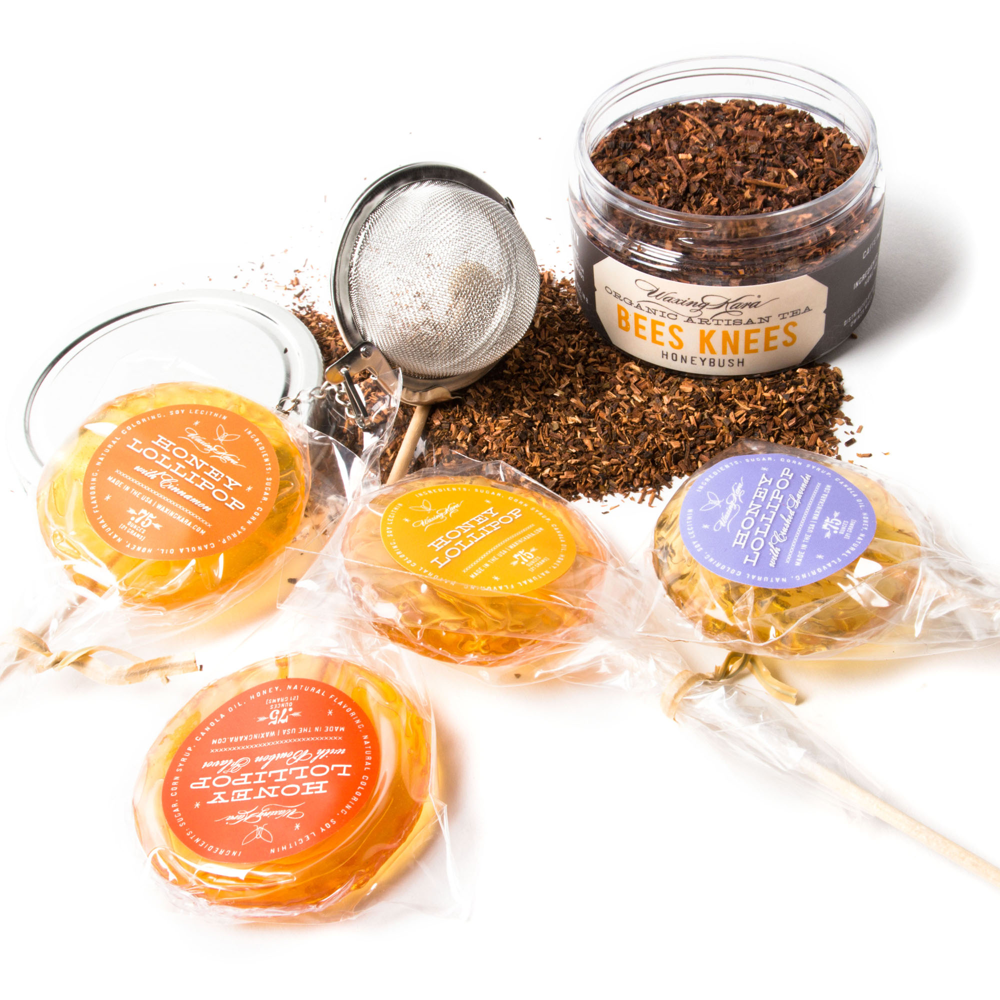 Tea Time to go contents loose leaf tea, four lollipops, stainless tea ball on table