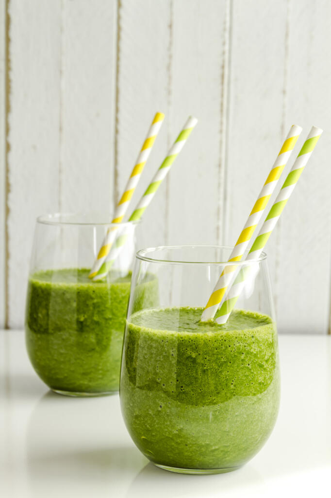 Two glasses filled with spinach and kale green detox smoothie with yellow and green swirled straws