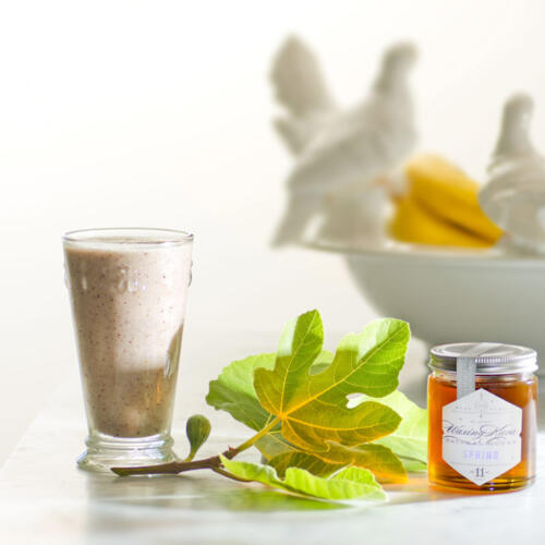 Honey Fig Smoothie in glass with fresh-picked fig leaf and fig in process on white marble counter with white bowl filled with bananas