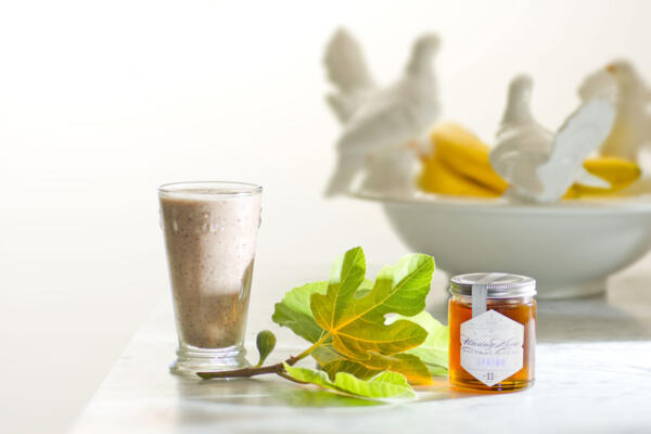 Fig smoothie in glass with fresh-picked fig leaf and fig in process on white marble counter with white bowl filled with bananas