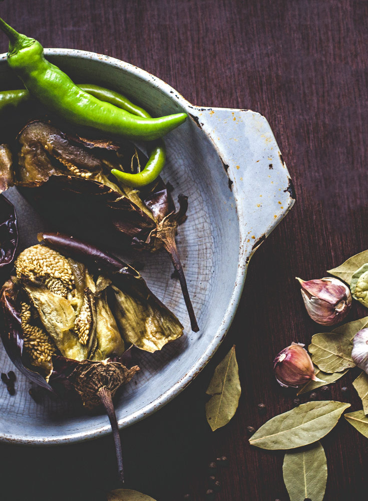 roasted eggplant with hot pepper on platter with fresh garlic on tabletop