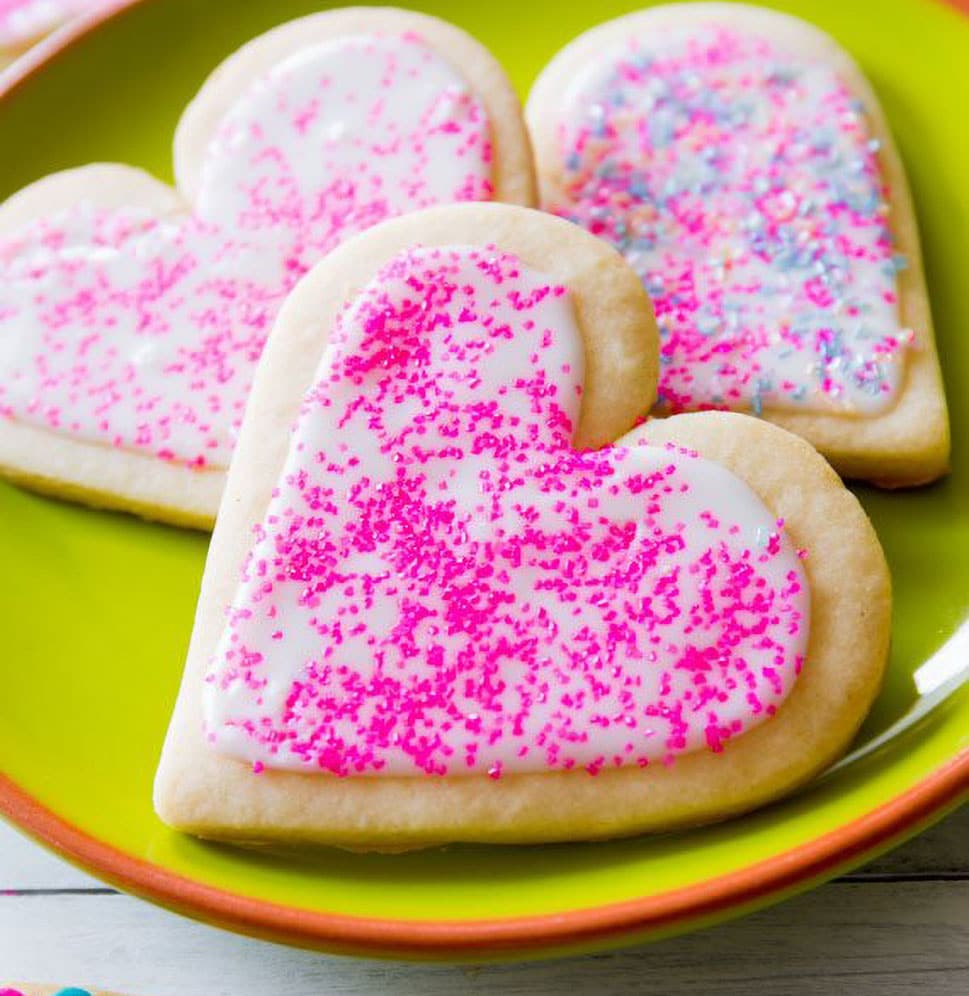 Sally's Baking Addiction Best Sugar Cookie Recipe pink heart sprinkled icing on sugar cookie on green plate