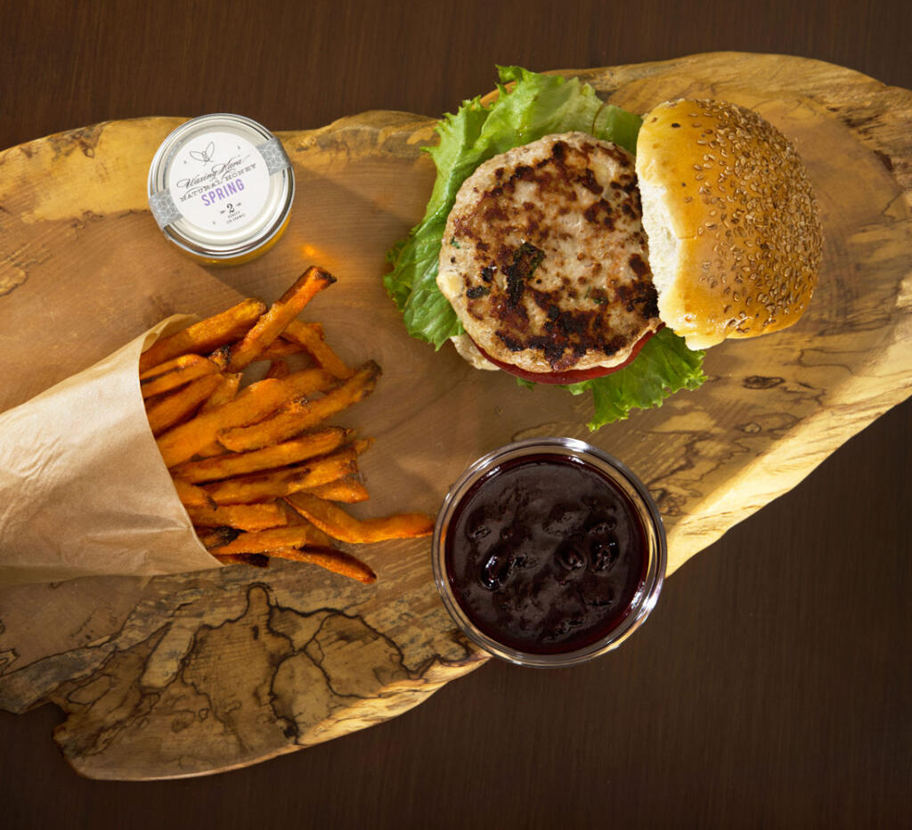 Overhead Turkey Burger with Blueberry Ketchup and sweet potato fries with small jar of Waxing Kara Spring Honey on live edge wood platter on table