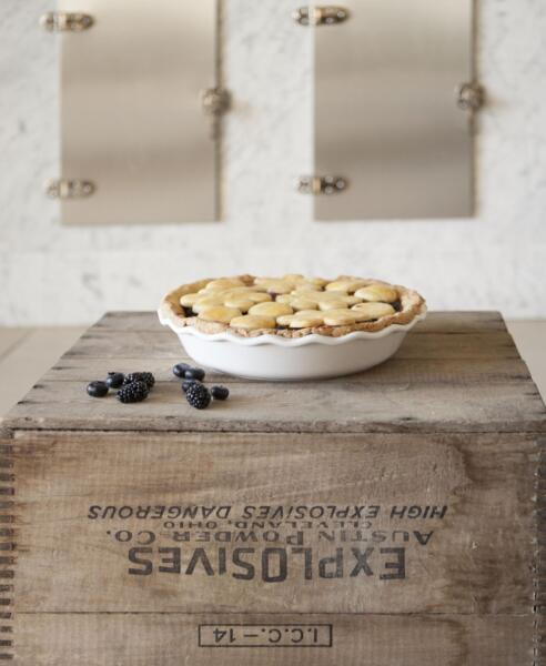 Bumbleberry Pie on an explosives bin in white pie plate with a few fresh-picked blueberries and blackberries in front of and old-style ice chest.