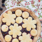 pie on napkin and wood plank table with fresh-picked berries on the side