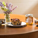 Healthy coffee cake set with honey, espresso and fresh picked wildflowers with bowl of fresh blueberries on wood stump table