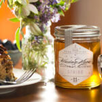 Healthy coffee cake on white plate with fork close-up on wood table with spring kosher honey and dramatic lighting with stainless cup of coffee and wildflower arrangement