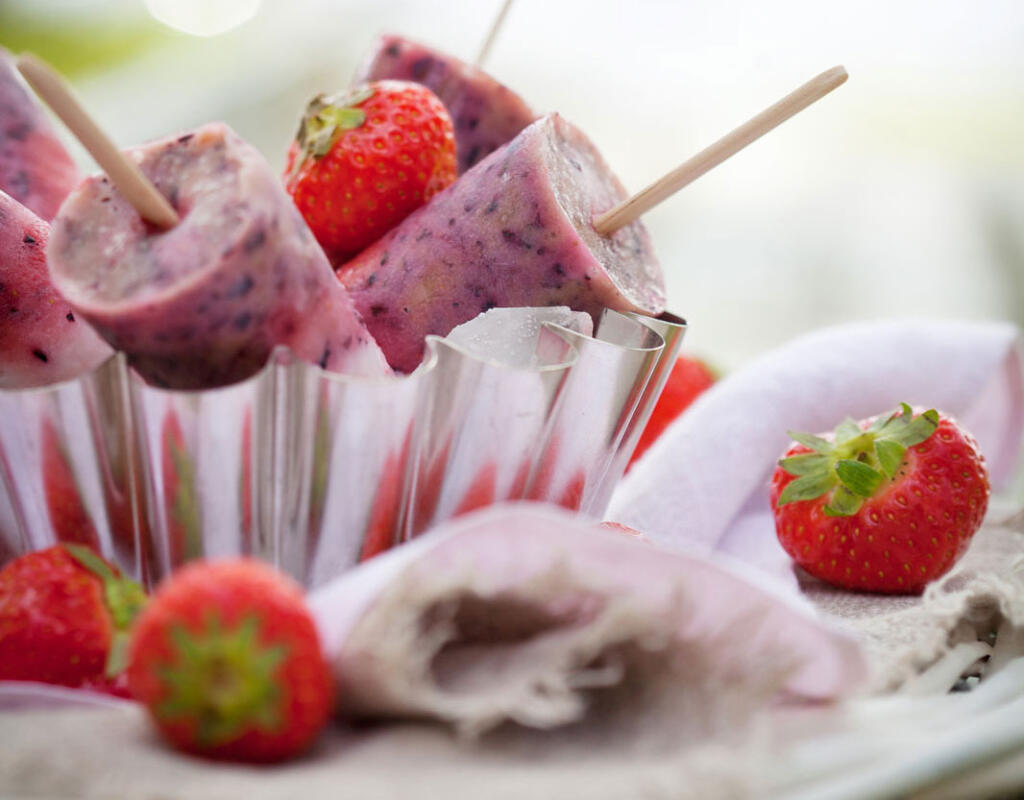homemade berry popsicles in paper cup with fresh berries on table with napkin