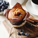 honey blueberry muffin on cutting board with fresh blueberrries and cinnamon sticks