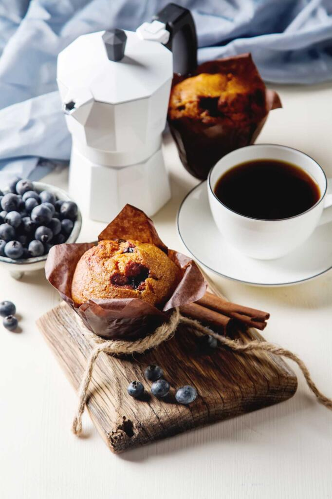 honey blueberry muffin on cutting board with cinnamon and blueberries and espresso pot and cup of coffee