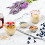 Simple overnight oats in weck jar topped with eastern shore honey and fresh berries on marble table with raw ingredients, fresh-picked blueberries, milk pitcher with napkin and fresh cut lavender.
