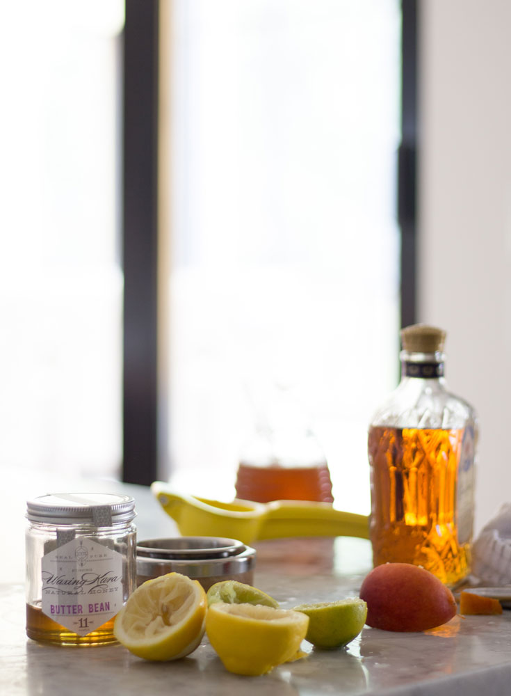 Kent Island test kitchen cooking behind the scenes. Mostly empty honey jar, lemon halves squeezed of all their juice, bottle of bourbon with some left on kitchen counter