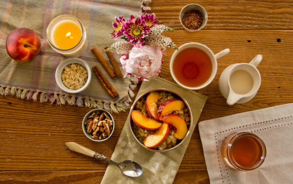 Warm Peach Oatmeal served with fresh peach slices and eastern shore honey with milk pitcher and side of nuts. Candle burning. Napkins and placemats and raw ingredients on the table with hot tea and bouquet of flowers