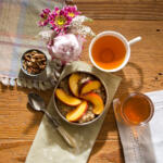 Warm Peach Oatmeal served with fresh peach slices and eastern shore honey with milk pitcher and side of nuts. Candle burning. Napkins and placemats on the table with hot tea and bouquet of flowers