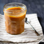 honey caramel sauce in glass jar on neutral striped napkin with spoon on wood table