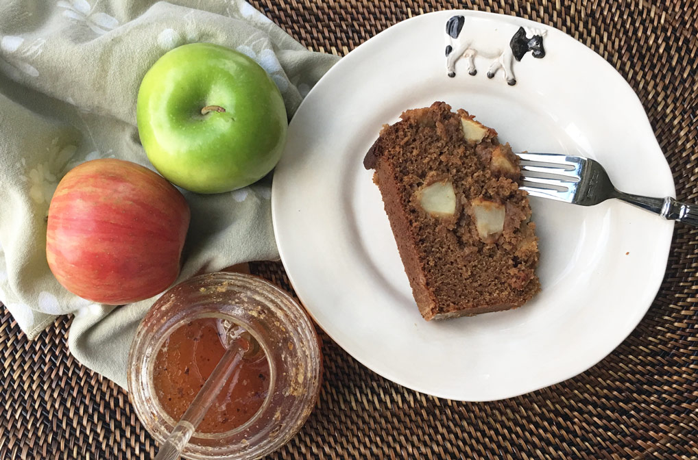 apple honey cake on cow plate with fork on wicker placemat with 2 apples a napkin and raw honey in hive container