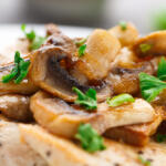 Chicken with sauteed mushrooms on plate up close
